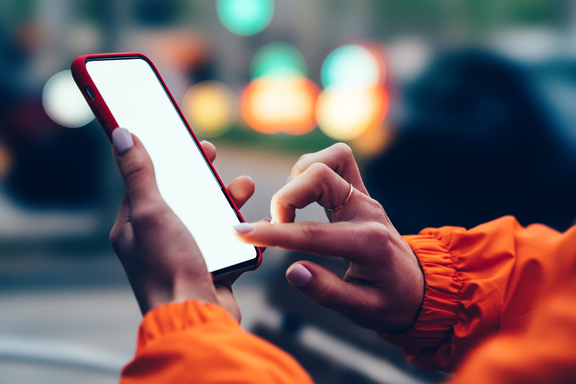 Close up view of female hands holding mobile phone touching mock up blank screen with finger. People using app on smartphone on street with bokeh blurred city lights. Texting message in social network